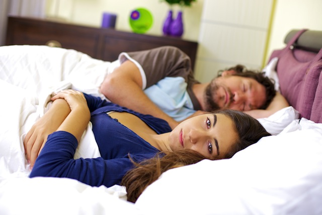 couple with relationship problems laying in bed